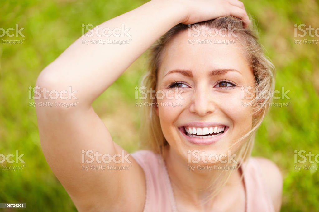 Cheerful young woman with hand on head against green background royalty-free stock photo