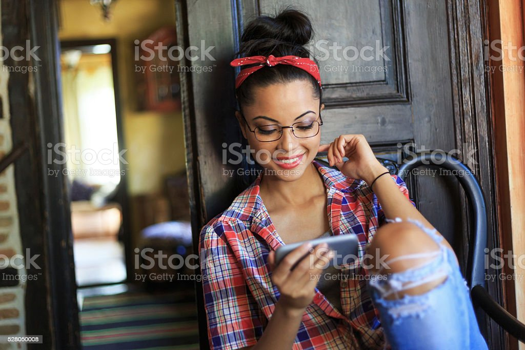 Cheerful young woman with headband using phone stock photo