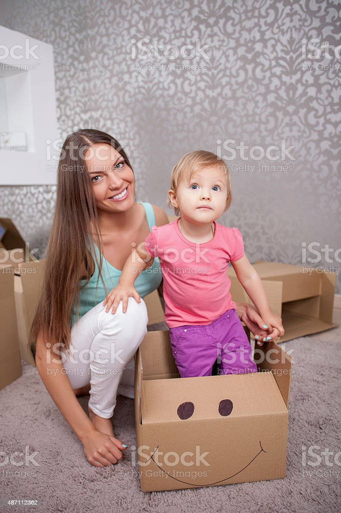 Cheerful young woman with her child are packing things stock photo