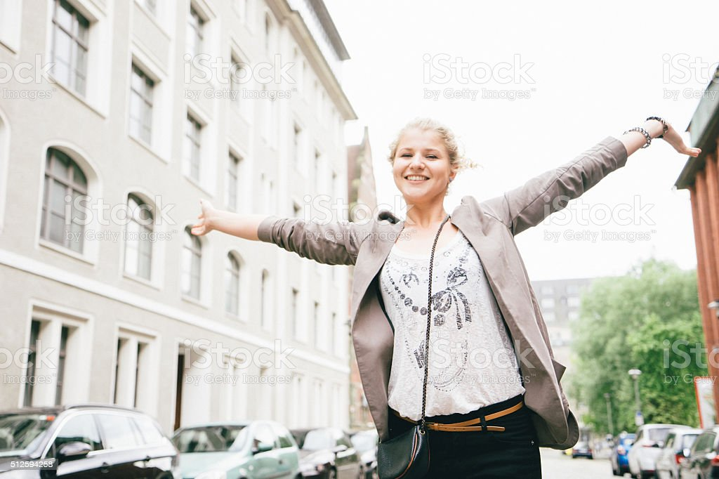 Cheerful Young Woman With Raised Arms, City Street On Background stock photo