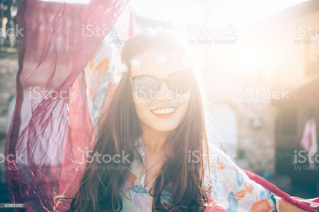 Cheerful young woman with wreath of daisies and sunglasses stock photo