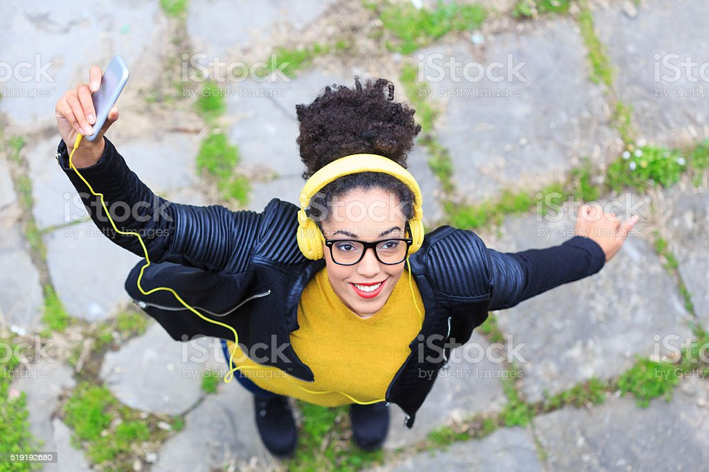 Cheerful young woman with yellow headphones listening music stock photo
