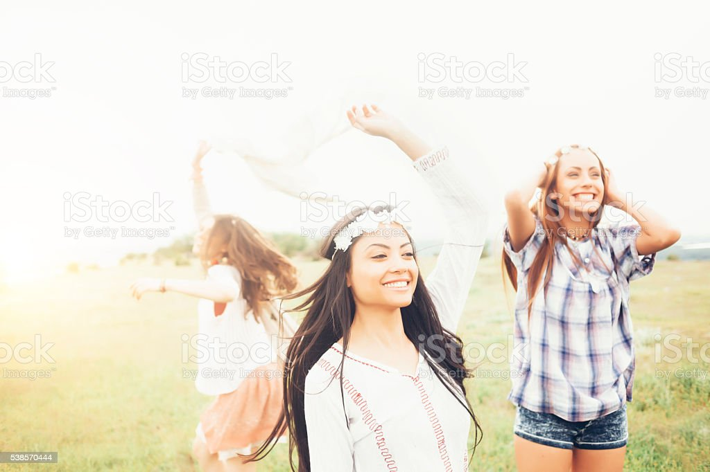 Cheerful young women dancing in the grassland stock photo