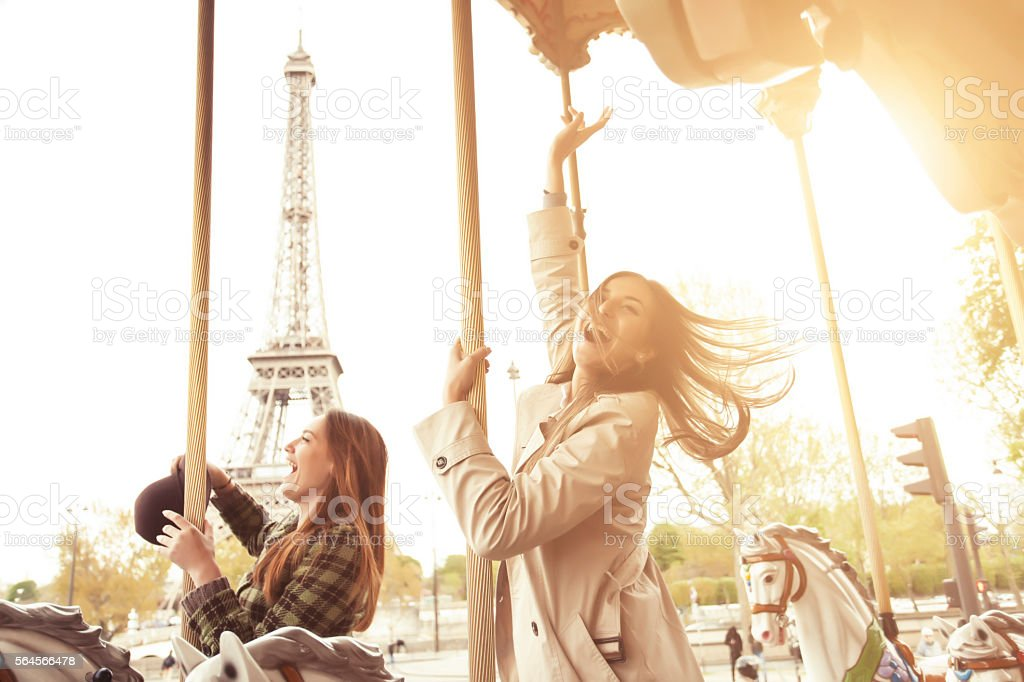 Cheerful young women having fun on carousel at Eiffel tower stock photo