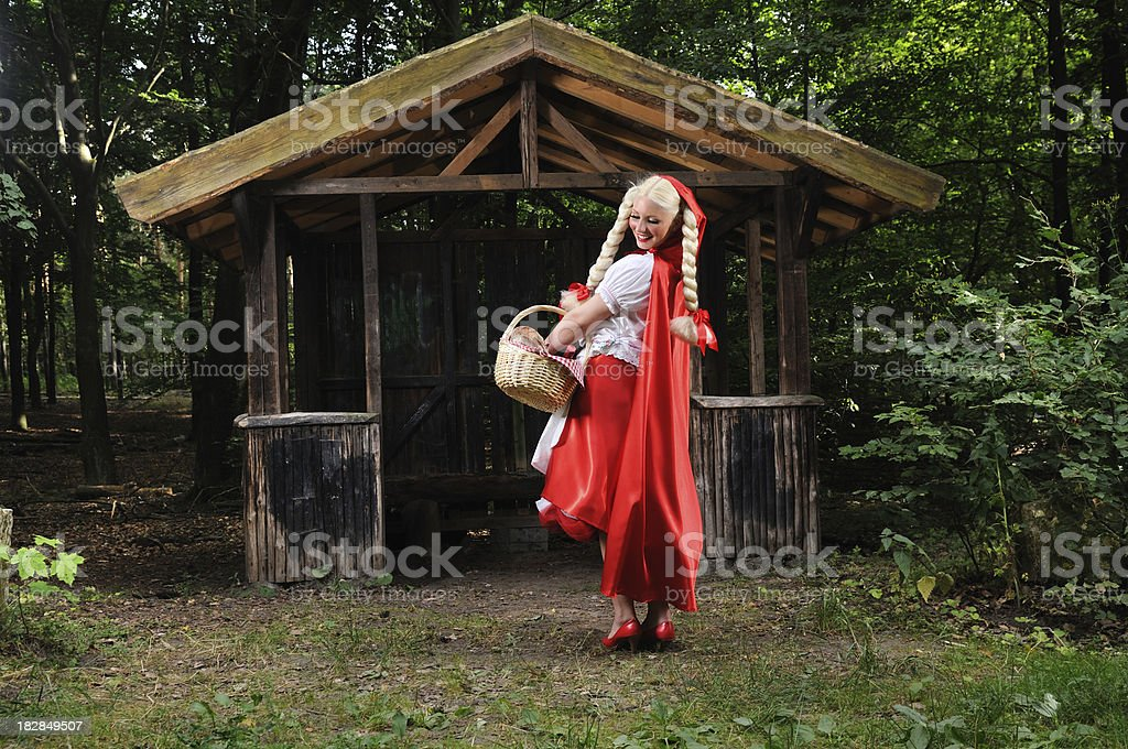 Cheerfull Little Red Riding Hood Checking Her Basket stock photo