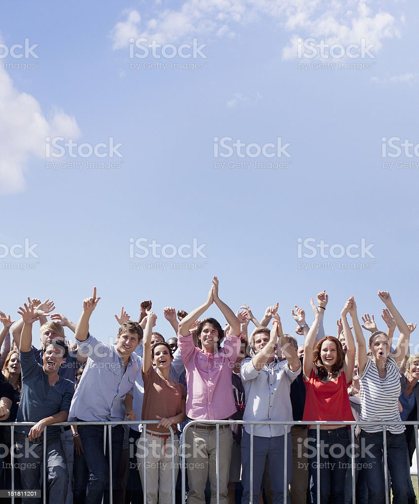Cheering crowd with arms raised stock photo