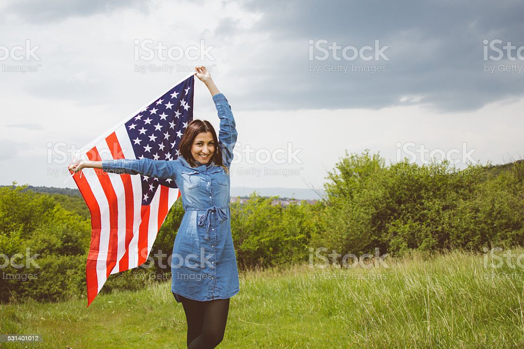 Cheering girl waving the American flag stock photo