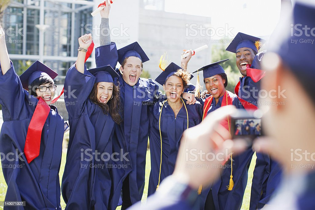 Cheering graduates taking picture of themselves royalty-free stock photo