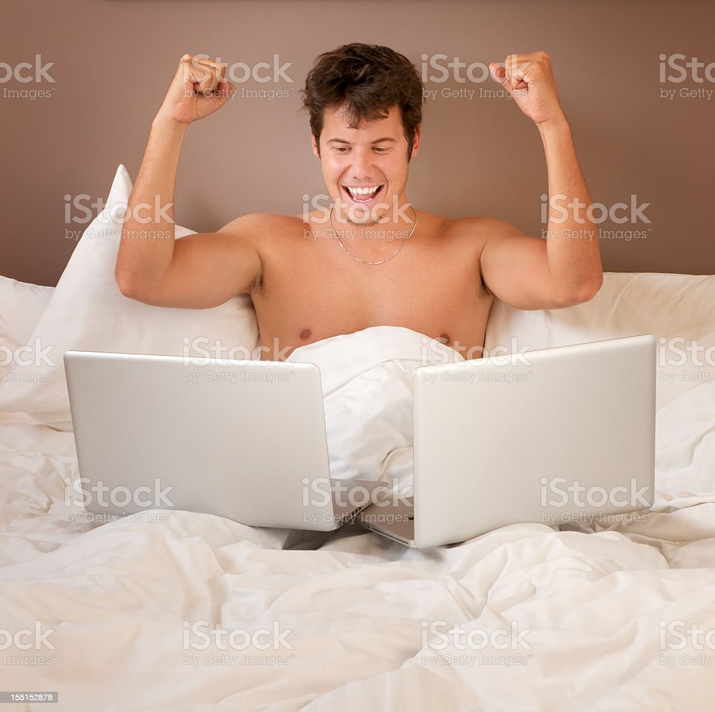 Cheering Guy with Laptop in Bed royalty-free stock photo