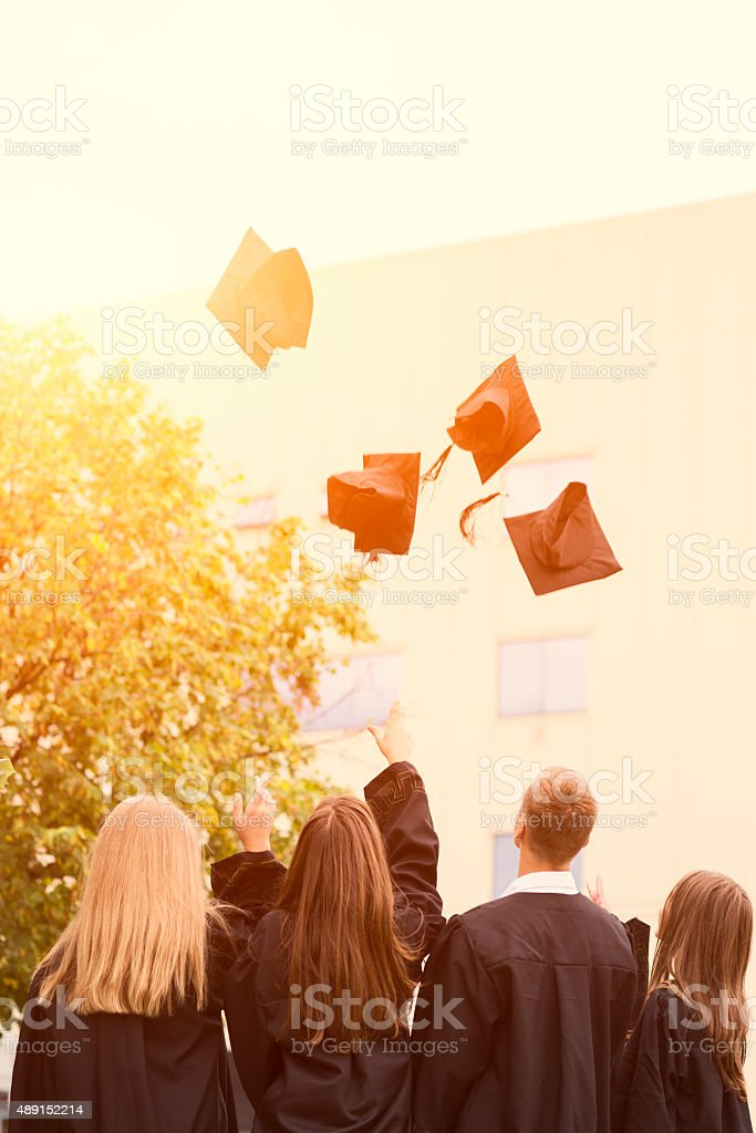 Cheering High School Graduates Throwing Caps Into Air. stock photo