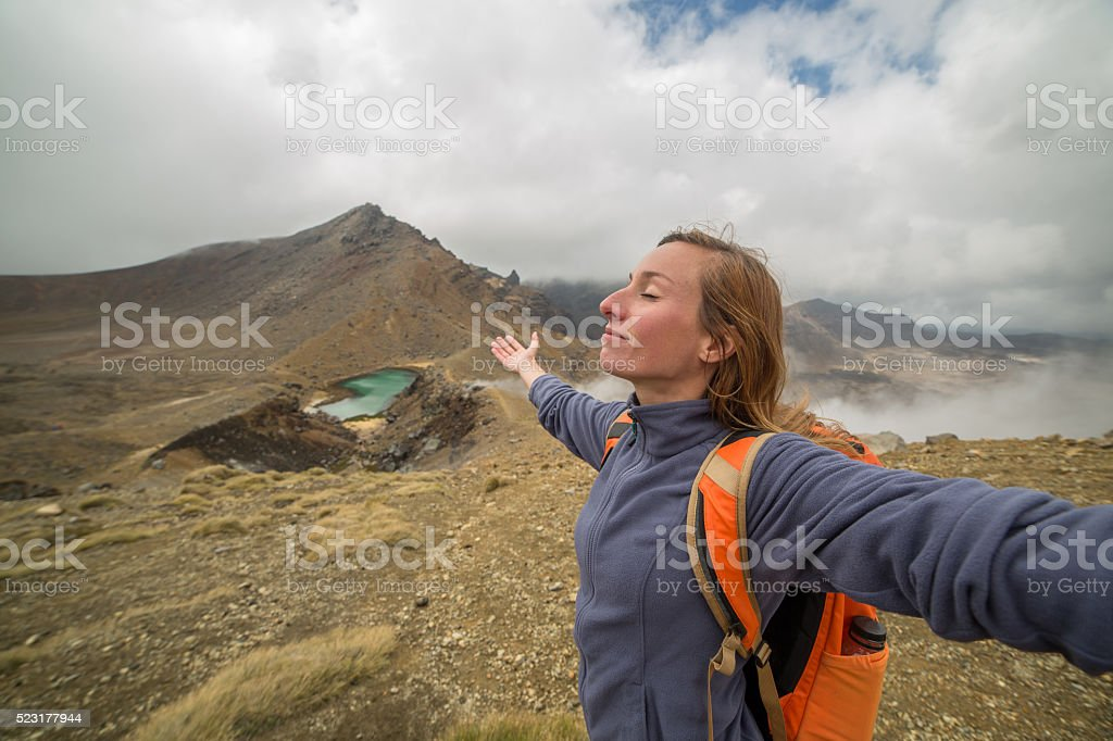 Cheering hiker arms outstretched on mountain top stock photo