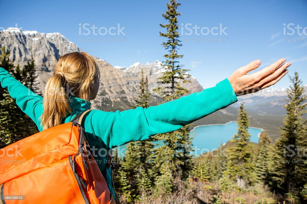 Cheering hiker at mountain top, arms outstretched stock photo