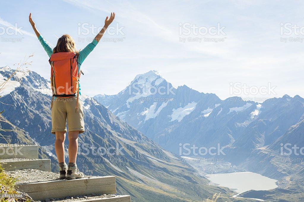 Cheering hiker on mountain top celebrates achievement stock photo