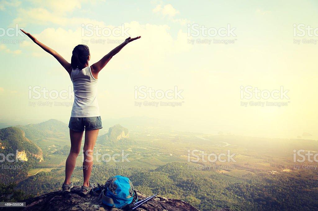 cheering hiking woman on mountain peak stock photo