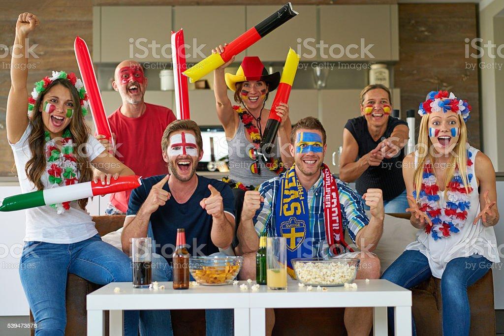 many happy international soccer fans watching tv