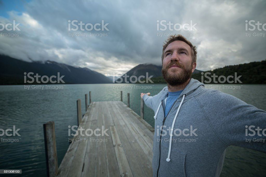 Cheering man embracing nature on lake pier stock photo