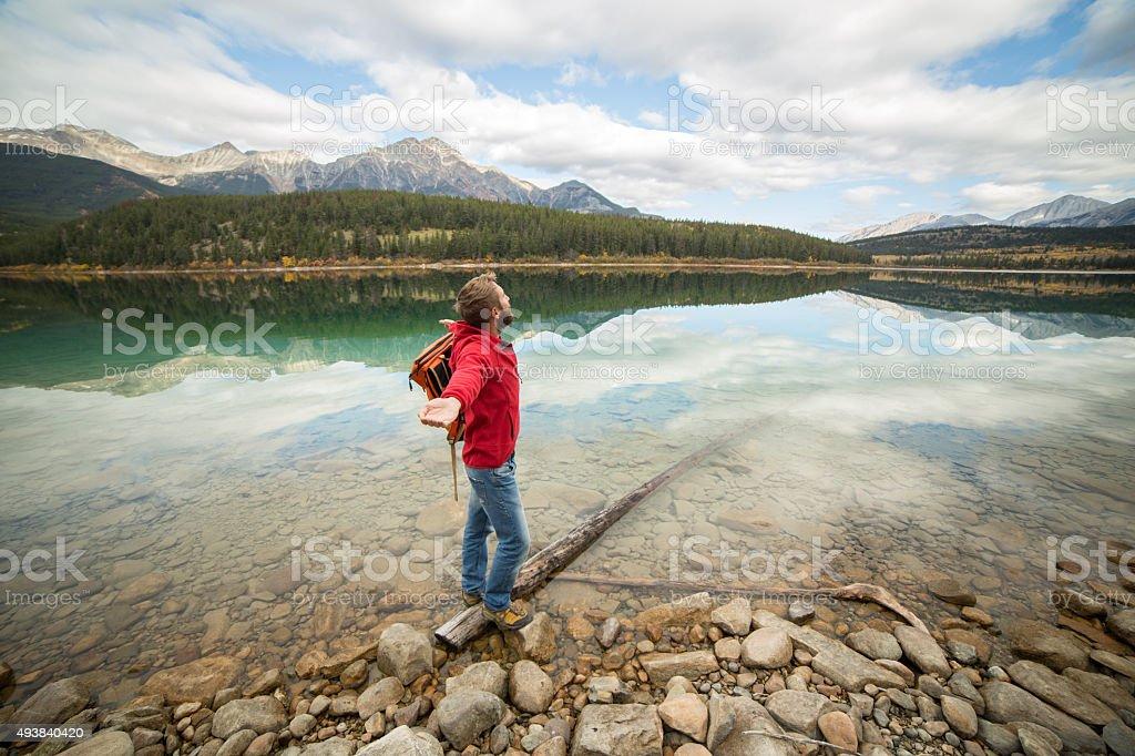 Cheering man standing on log enjoying nature stock photo
