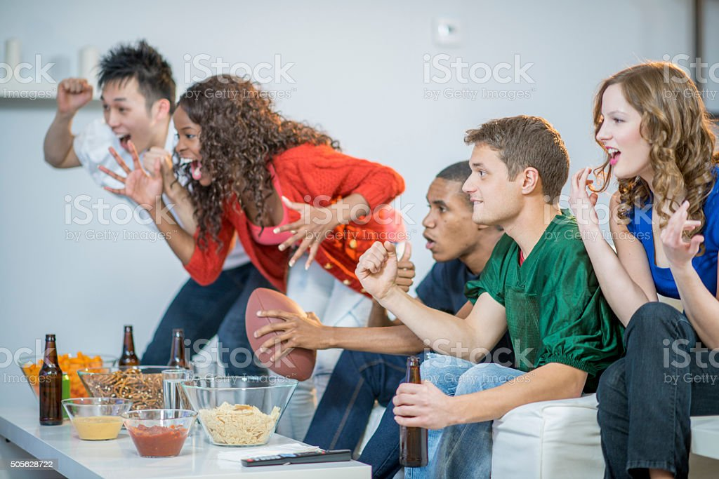 Cheering on Their Football Team During the Superbowl stock photo