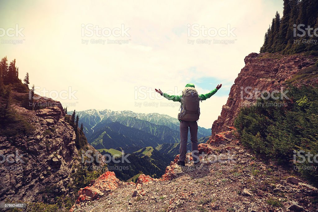 cheering successful woman backpacker open arms on mountain peak stock photo