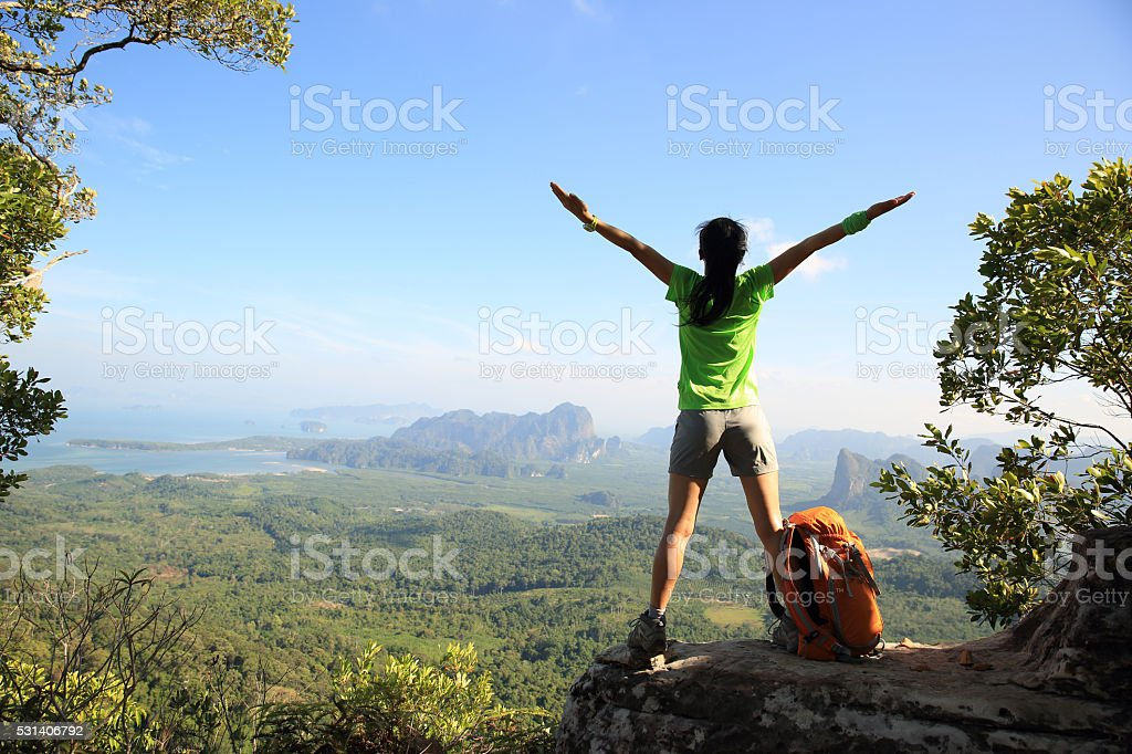 cheering successful woman hiker open arms at mountain peak stock photo