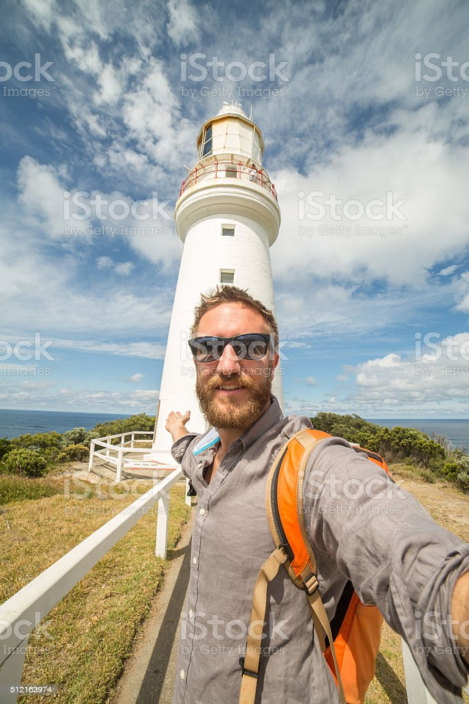 Cheering tourist man takes selfie portrait with Cape Otway lighthouse stock photo