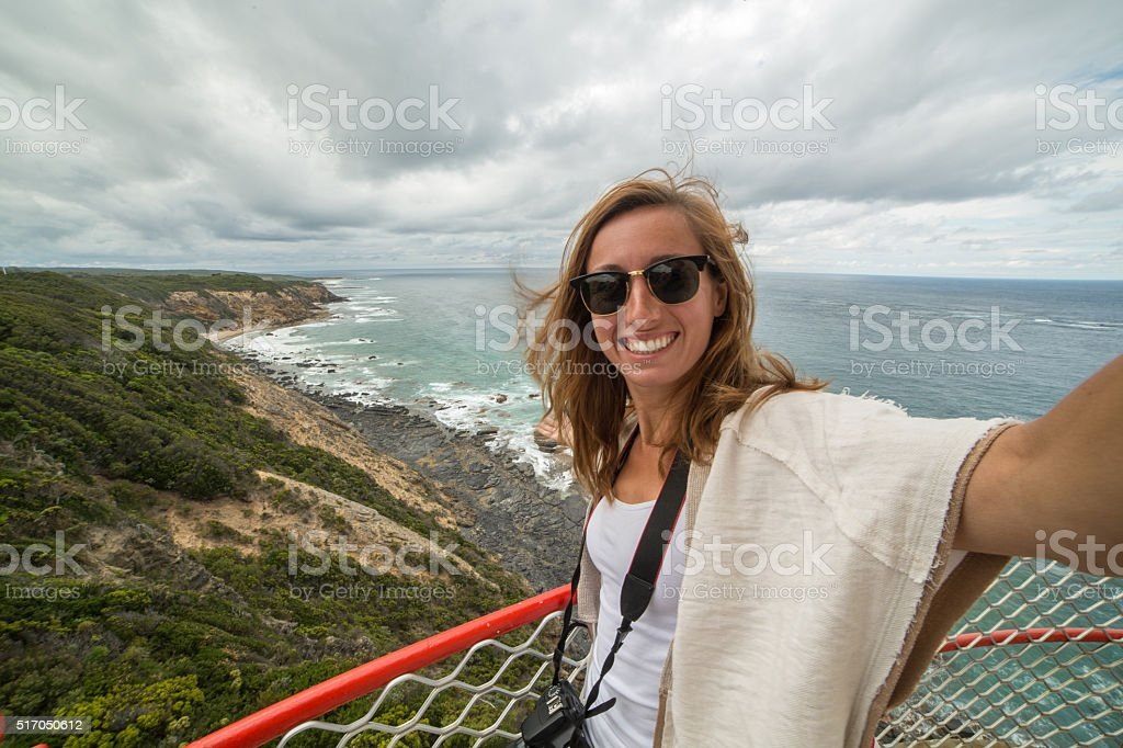 Cheering tourist woman takes a selfie portrait from lighthouse stock photo