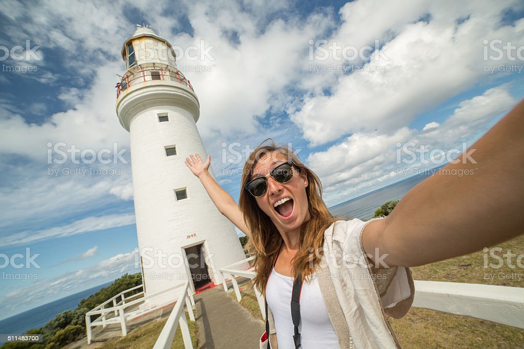 Cheering tourist woman takes selfie portrait with lighthouse stock photo