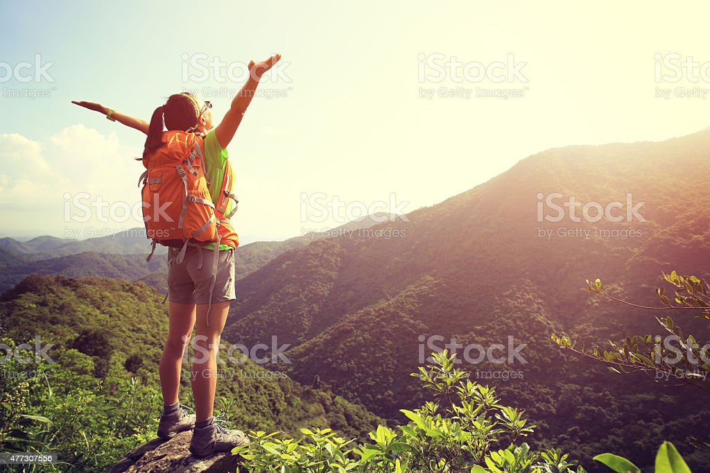 cheering woman hiker open arms at mountain peak cliff stock photo