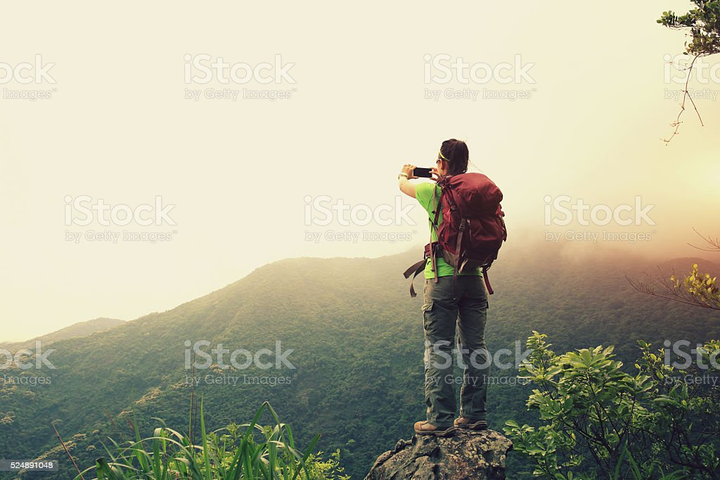 cheering woman hiker taking photo with smartphone stock photo