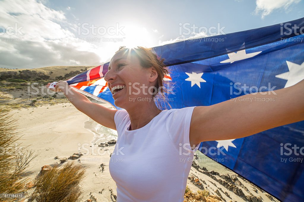 Cheering woman on beach holding Australian's flag stock photo