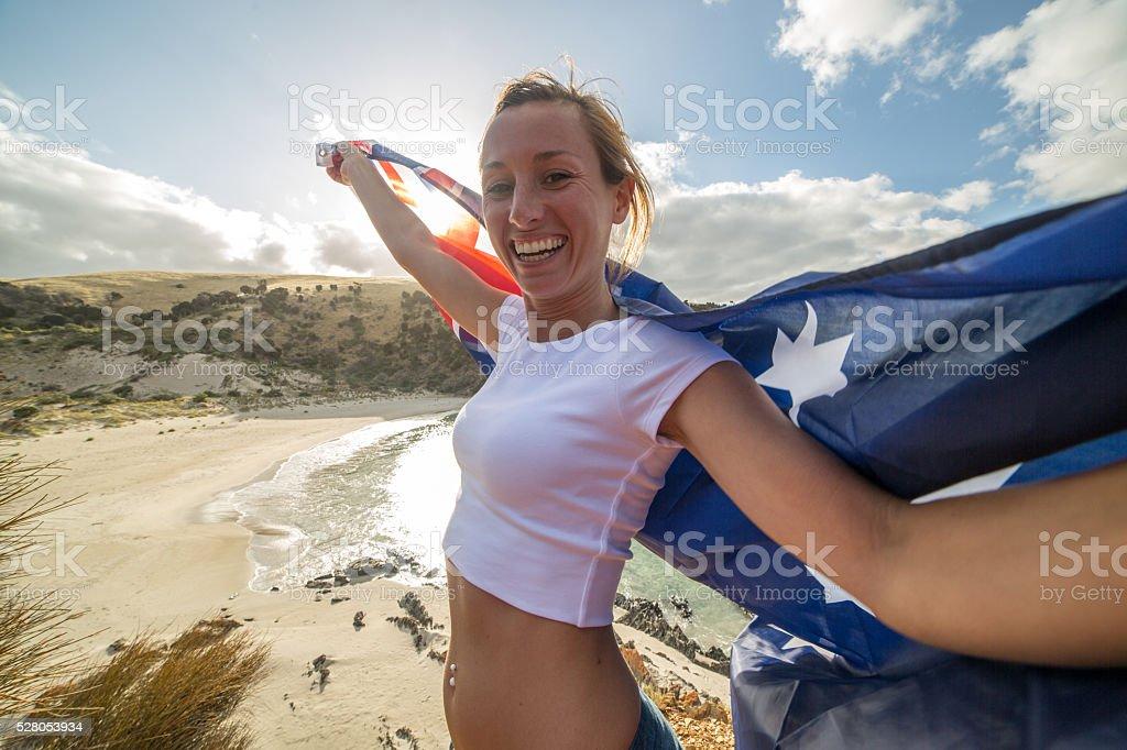 Cheering woman on beach holding Australian's flag stock photo