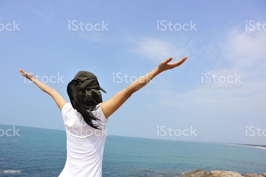 cheering woman open arms at seaside, summer holidays stock photo