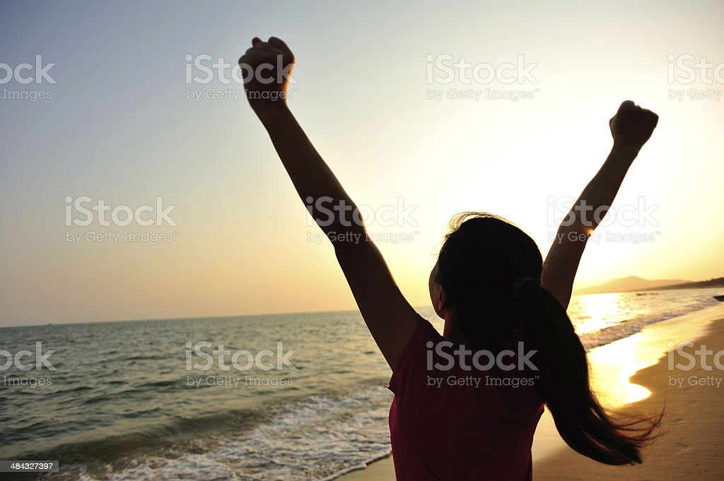 cheering woman open arms to sunrise at sea stock photo