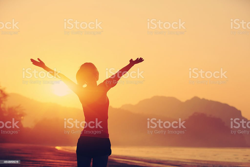 cheering woman open arms to sunrise at seaside stock photo