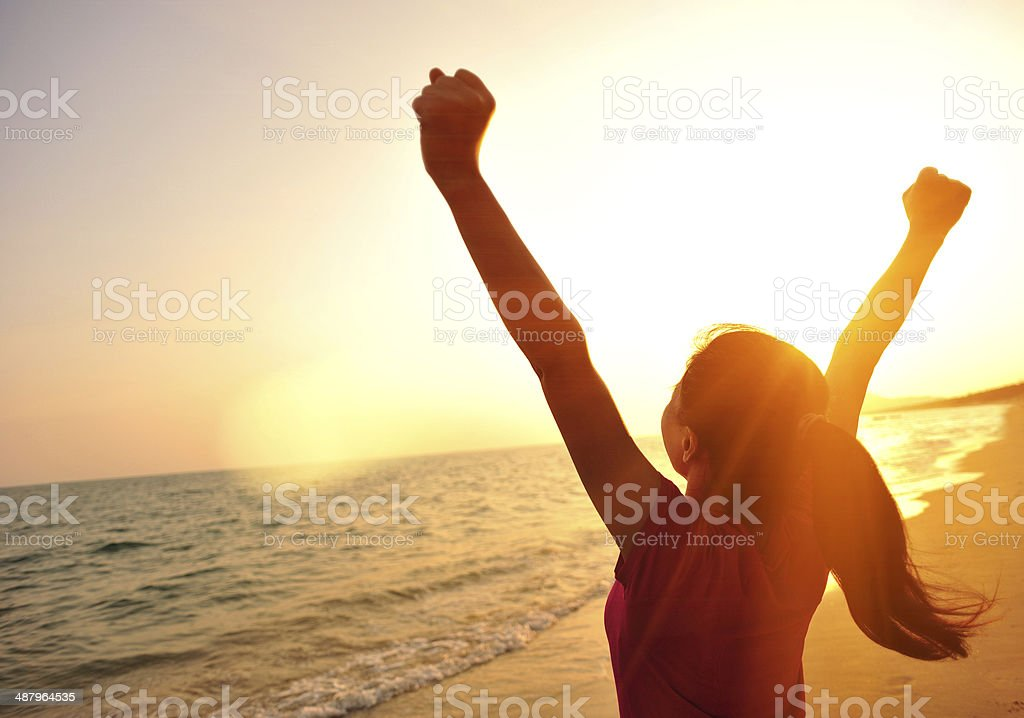 cheering woman open arms to sunset at seaside stock photo