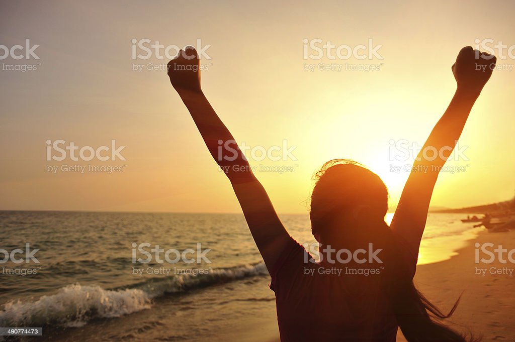 cheering woman open arms to sunset at seaside royalty-free stock photo