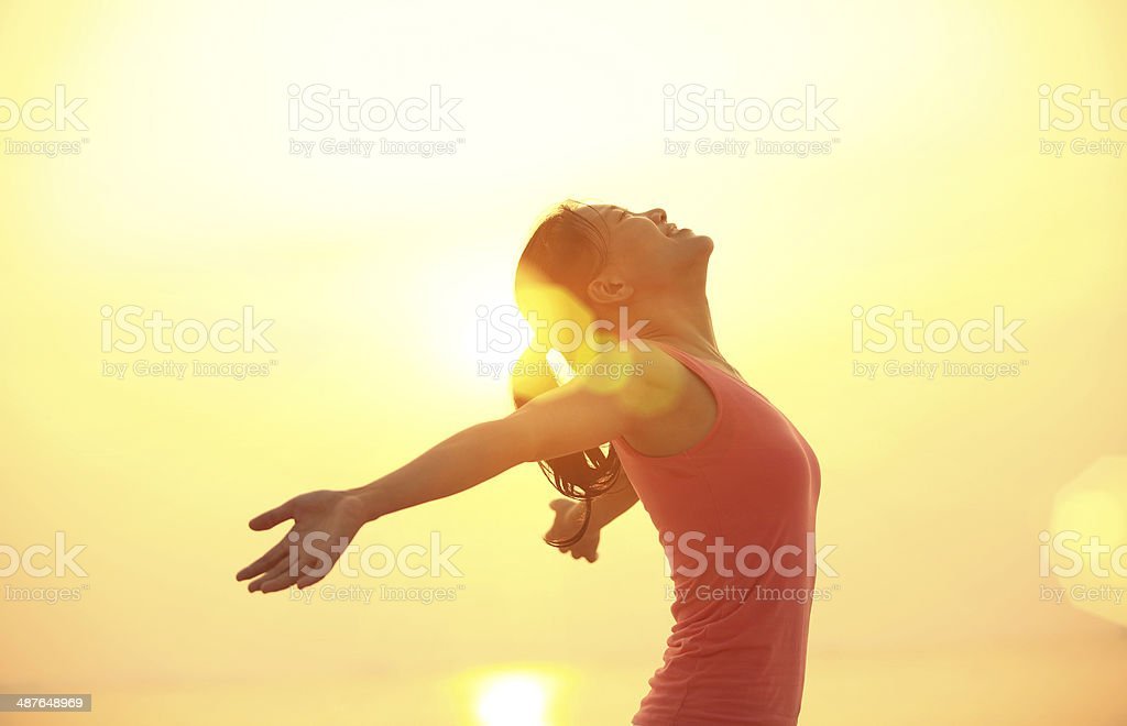 cheering woman open arms under  sunrise on beach stock photo