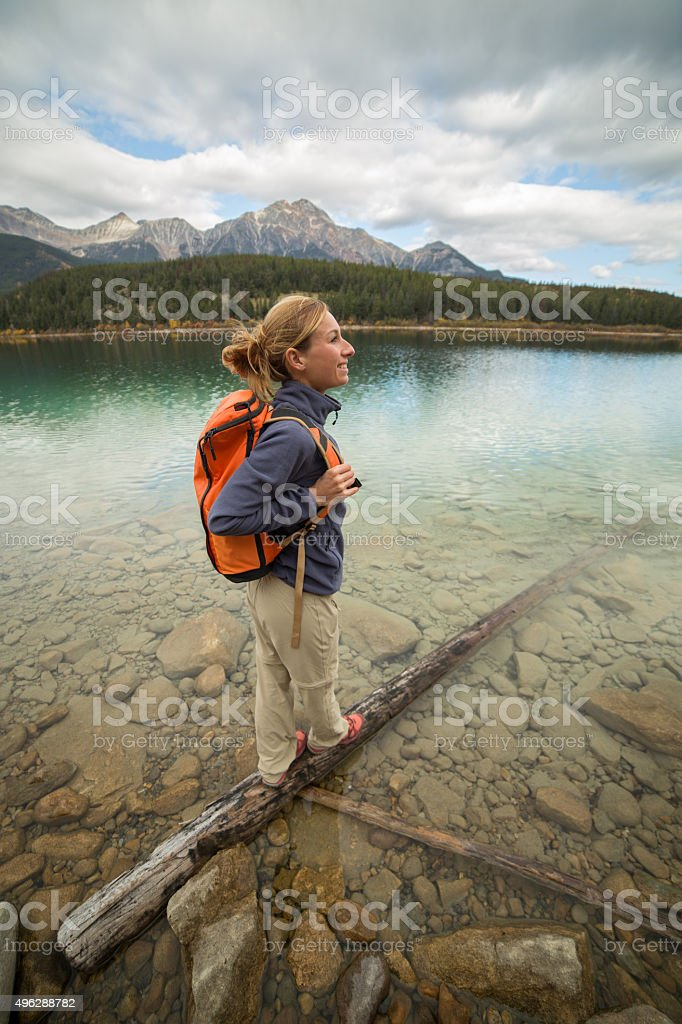 Cheering woman standing on tree log above lake stock photo