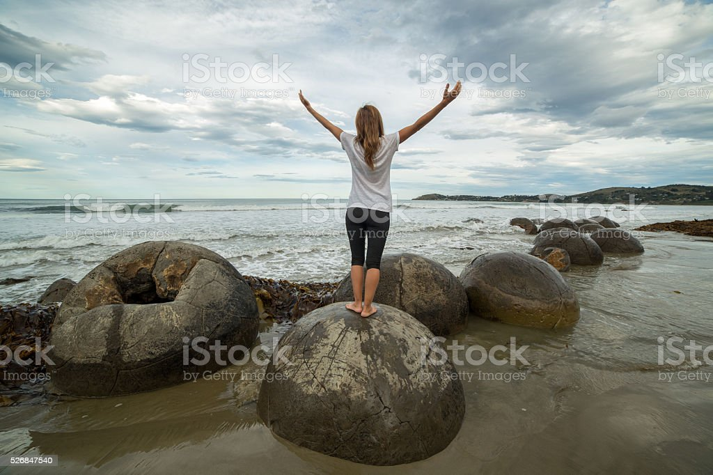 Cheering woman stands on spheric boulder by the sea stock photo