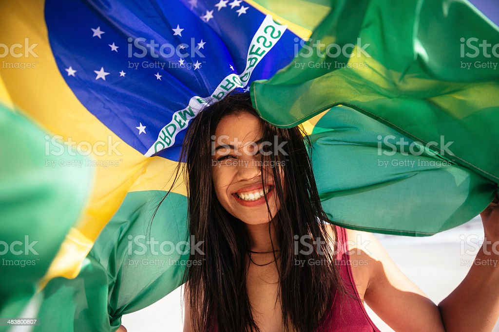 Cheering woman under brazilian flag stock photo