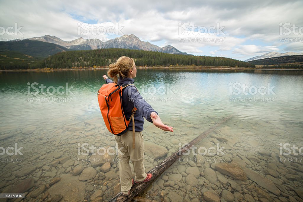 Cheering woman walking on log arms outstretched stock photo