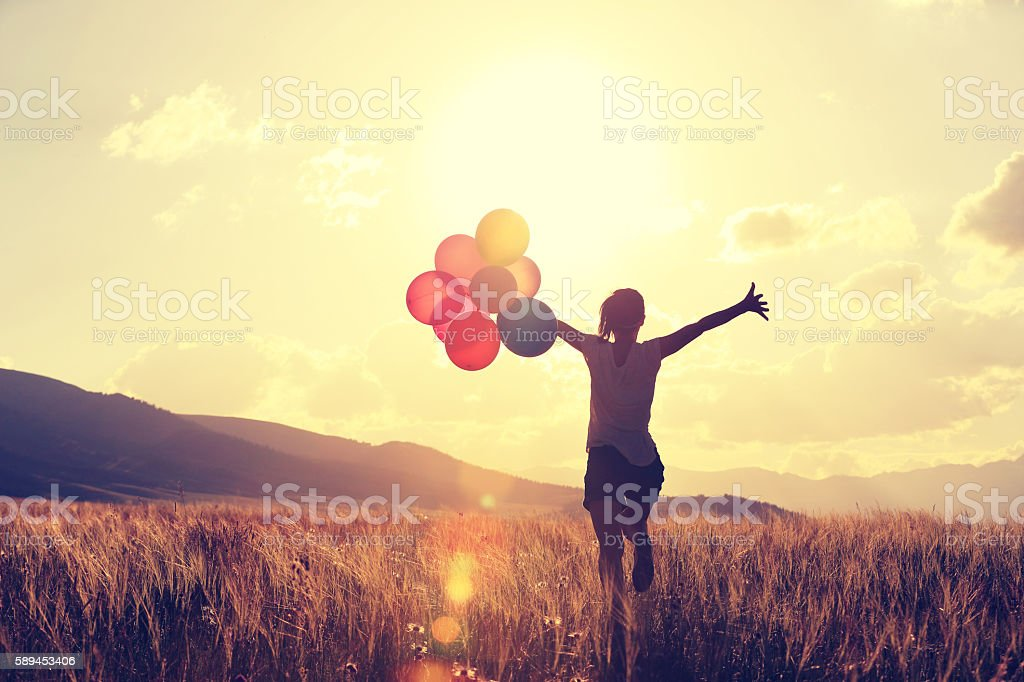 cheering young asian woman on grassland with colored balloons stock photo