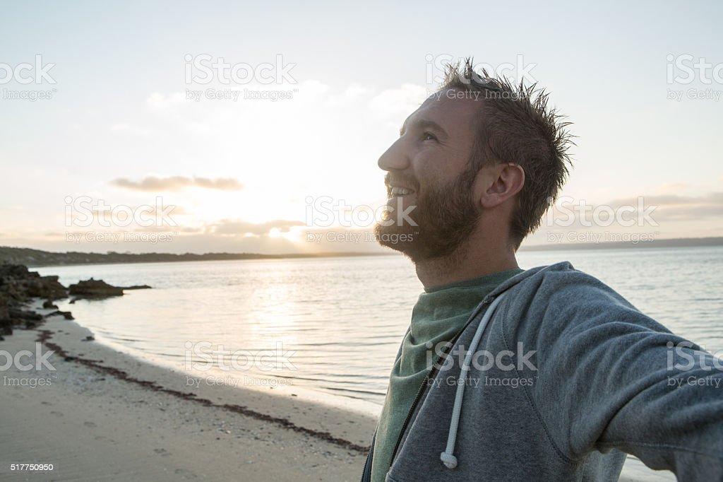 Jubeln junger Mann Ausgestreckte Arme am Strand ein Sonnenuntergang – Foto