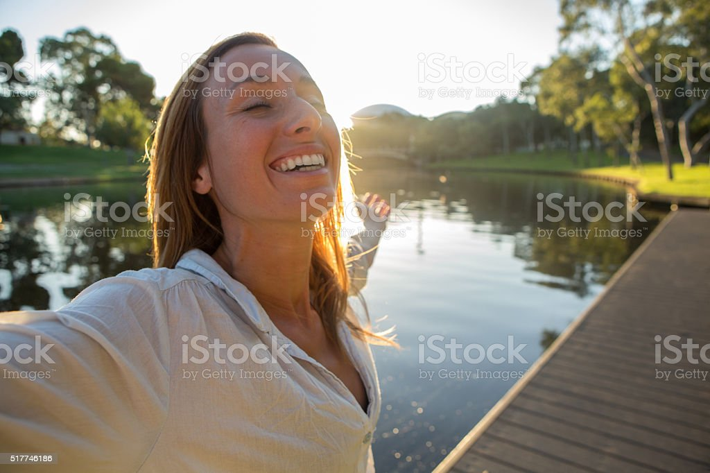Cheering young woman arms outstretched in Adelaide botanic garden stock photo