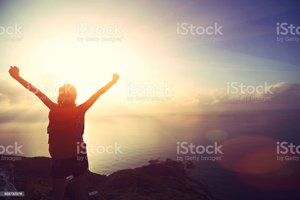 cheering young woman backpacker at sunrise seaside mountain peak stock photo