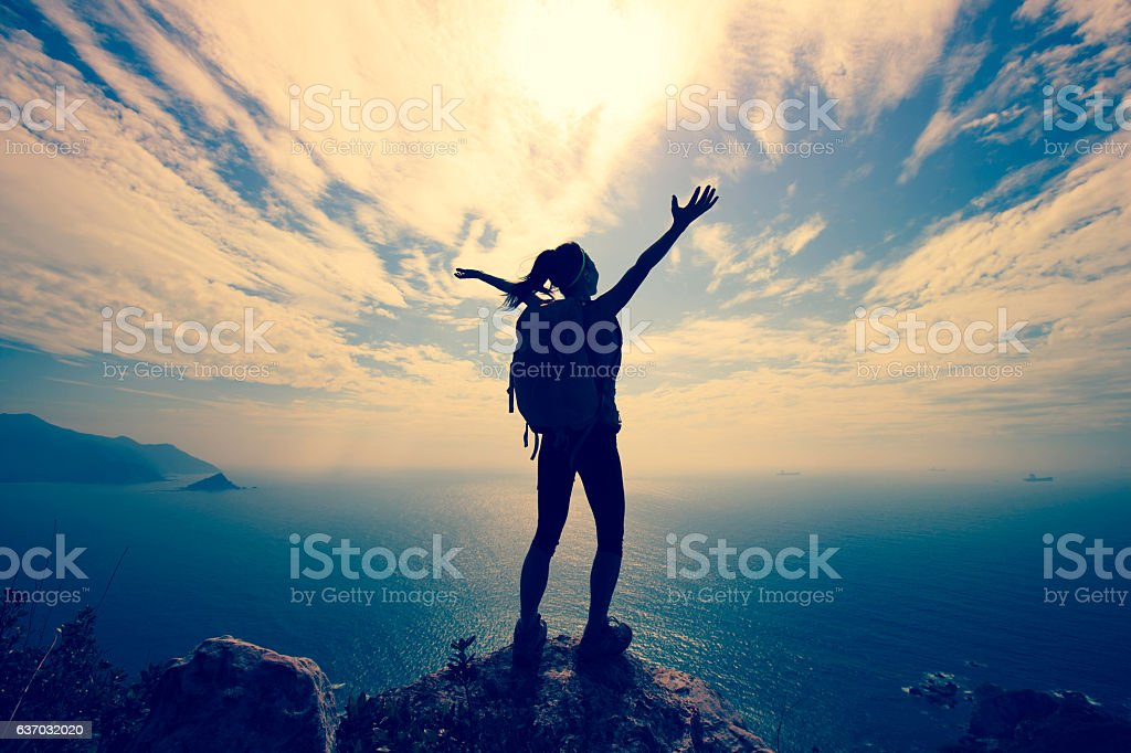 cheering young woman hiker at seaside mountain peak stock photo