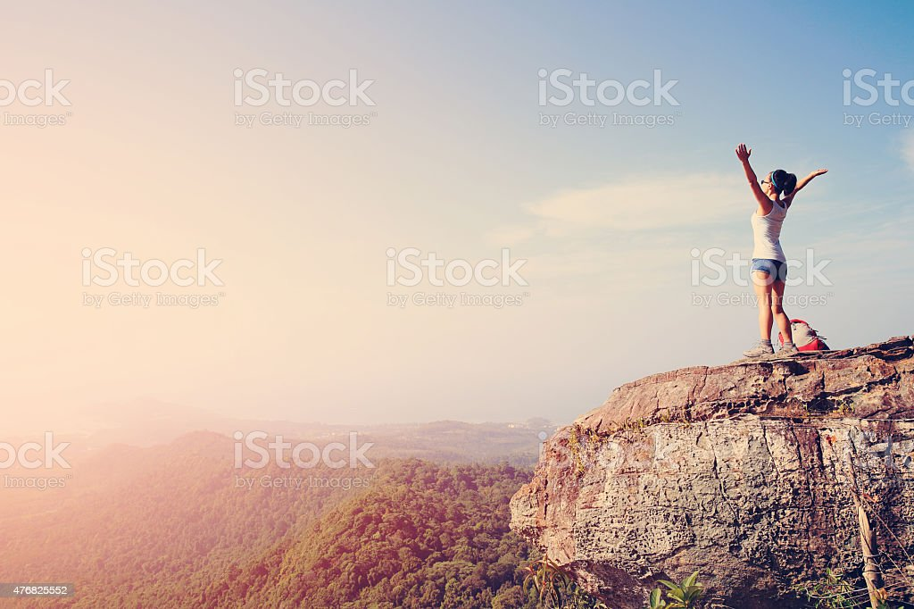 cheering young woman hiker open arms at mountain peak stock photo
