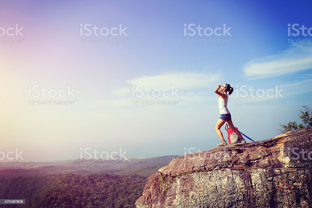 cheering young woman hiker yelling  at mountain peak stock photo