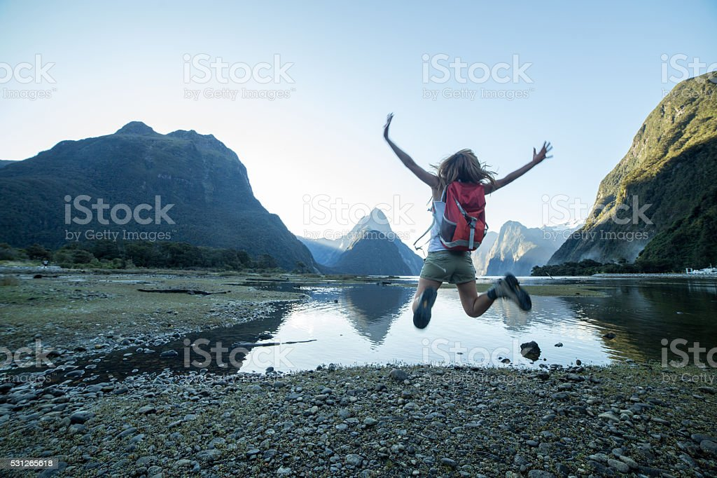 Cheering young woman jumps at Mitre peak-Milford sound, NZ stock photo