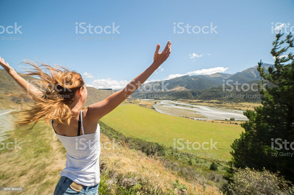 Cheering young woman on hill arms outstretched facing strong wind stock photo
